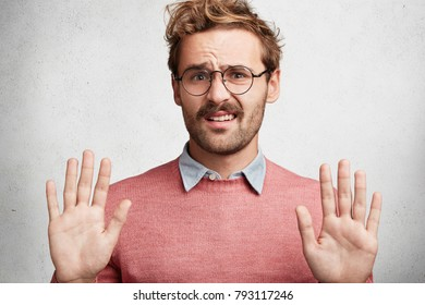 Handsome young male refuses offer, gestures indoor, shows his disapproval, keeps palms in front, demonstrates rejection or stop sign, isolated over white concrete background. Refusal concept