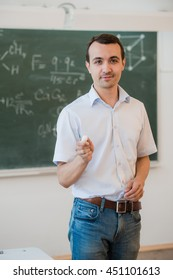 Handsome young male student or teacher standing relaxing against a green blackboard