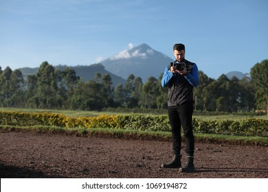 Handsome young male wearing a vest holding a camera with beautiful volcano in background