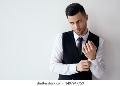Handsome young man adjusting his sleeves and fixing his cufflinks against white background with copy space