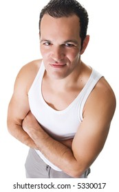 A handsome young man after working out, wearing a sleeveless shirt, standing with arms crossed with a smile.