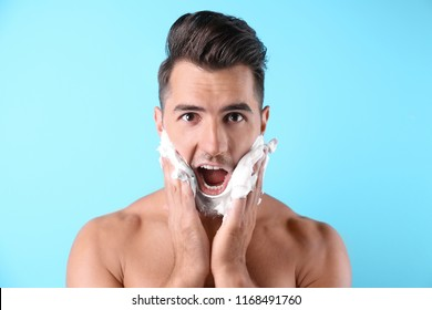 Handsome young man applying shaving foam on color background