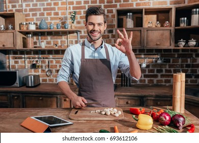 handsome young man in apron showing okay sign while cooking