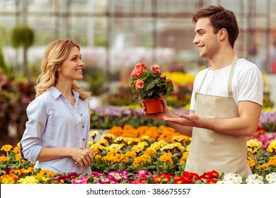 Handsome young man in apron is smiling while offering plants to woman in orangery