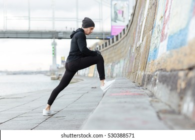 Handsome young man athlete stretching and exercising outdoors