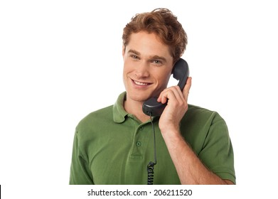 Handsome young man attending phone call