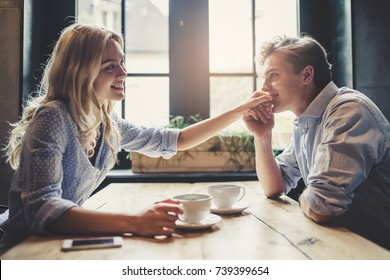 Handsome young man and attractive young woman are spending time together. Romantic couple in cafe is drinking coffee and enjoying being together. Man is kissing hand of his beloved woman.