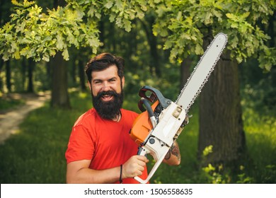 Handsome young man with axe near forest. The Lumberjack working in a forest. Logging