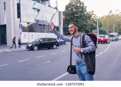 Handsome Young Man with Backpack Waving for a Taxi Ride