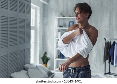 Handsome young man with bare torso is putting on a t-shirt and smiling while getting dressed at home