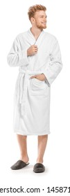 Handsome young man in bathrobe on white background