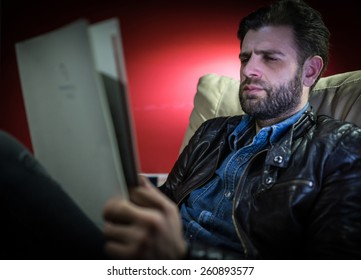 Handsome young man with beard reading magazine