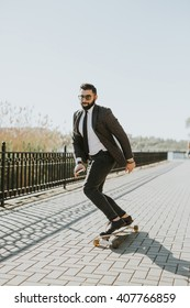 handsome young man with beard and sunglasses smart look office style boarding in the street and park