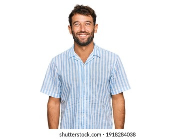 Handsome young man with beard wearing casual fresh shirt with a happy and cool smile on face. lucky person.