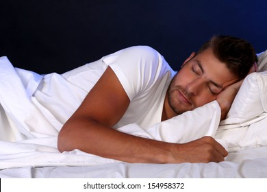 Handsome young man in bed