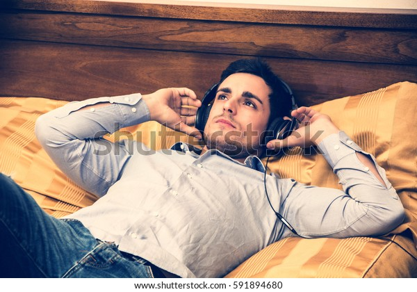 Handsome young man in bed listening to music with headphones, using cell phone or MP3 player