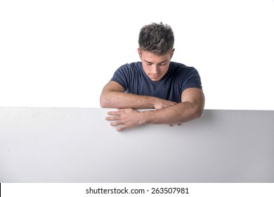 Handsome young man behind a blank horizontal white banner looking at copyspace, on white background