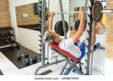 Handsome young man at the bench press lifting a barbell on an incline bench