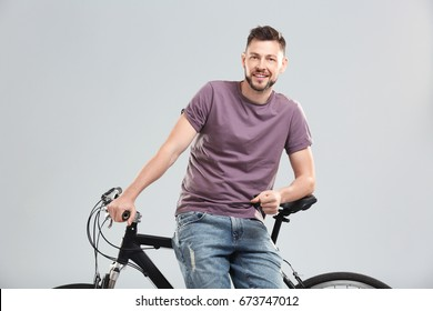 Handsome young man with bicycle on light background