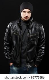 Handsome young man in black leather jacket, studio portrait