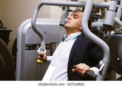 Handsome young man in a black suit, white shirt and tie training in the gym