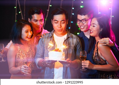 Handsome young man blowing candles on birthday cake at his party