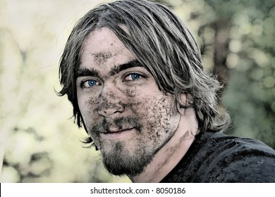Handsome young man with blue eyes has his face covered with mud after negotiating a particularly muddy ATV trail.