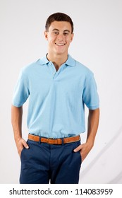 Handsome young man in blue shirt, stand with his hands in his pockets and a pleasing, friendly smile
