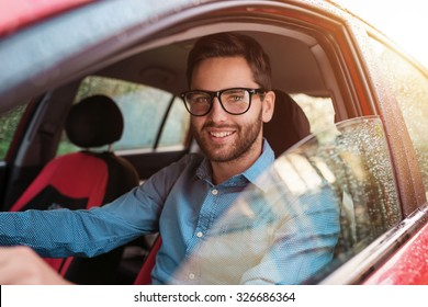Handsome young man in a blue shirt driving a car