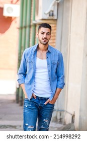 handsome young man in bluejeans outside on the street