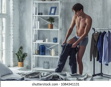 Handsome young man in boxer briefs is pulling on his pants while getting dressed at home