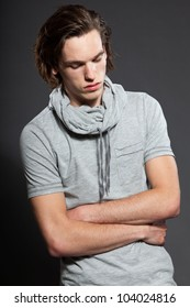 Handsome young man with brown long hair wearing grey shirt isolated on grey background. Fashion studio shot. Expressive face.