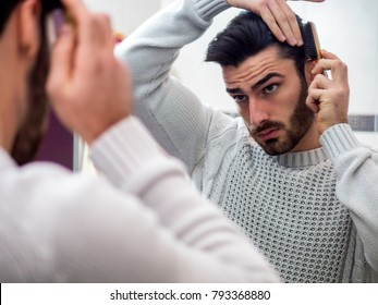 Handsome Young Man Brushing and Combing Hair in Mirror Getting Ready to Go Out