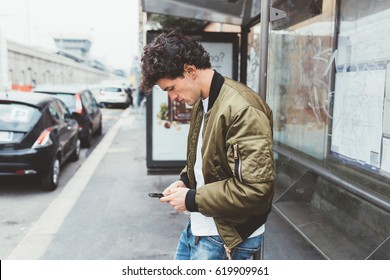 Handsome young man at bus stop using smart phone hand hold - social network, commuting, technology concept