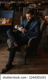 handsome young man in business clothes sitting in a cafe