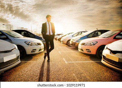Handsome young man in a business suit choosing a car in the car market