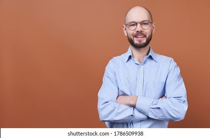 A handsome young man, a businessman, bald, with a beard, in round glasses and a striped shirt, crossed his arms on his chest and looks straight. Close-up of the face of happy successful business man.