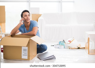 Handsome young man calling on the phone when packing his belongings
