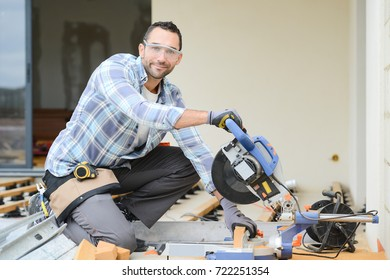 handsome young man carpenter using a circular saw while installing wood floor terrace outdoor in new house construction site