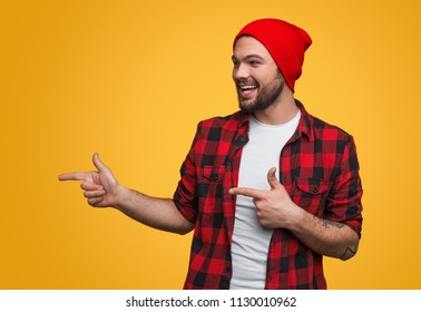 Handsome young man in casual outfit cheerfully smiling and pointing left while standing on bright yellow background