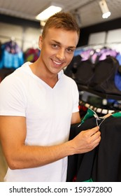 Handsome young man choosing sports wear in a sport outlet