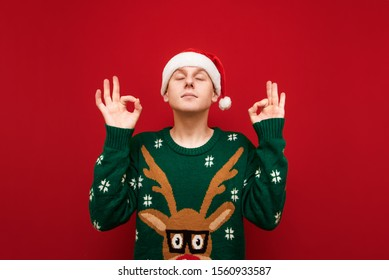 Handsome young man in christmas clothes meditates on a red background with his eyes closed, raised his hands and head up, wears a santa hat and a green warm sweater. Christmas yoga.