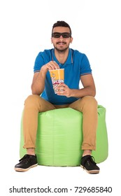 Handsome young man with a cinema glasses  sitting on green chair and eating popcorn, guy wearing blue t-shirt and beige pants, isolated on white background