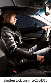 Handsome young man in coat on drivers seat riding sedan