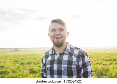 Handsome young man at countryside, in front of field wearing shirt, looking to camera smiling