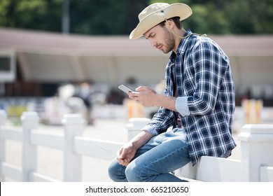 Handsome young man in cowboy hat using smartphone while sitting on wooden fence