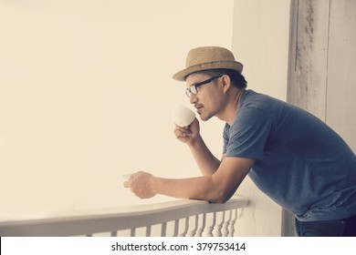 handsome young man with cup of coffee, enjoying life on outside balcony