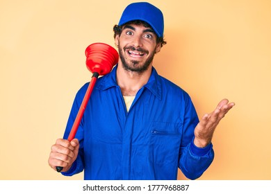 Handsome young man with curly hair and bear wearing plumber uniform holding toilet plunger celebrating achievement with happy smile and winner expression with raised hand