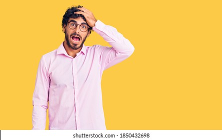 Handsome young man with curly hair and bear wearing business clothes surprised with hand on head for mistake, remember error. forgot, bad memory concept.