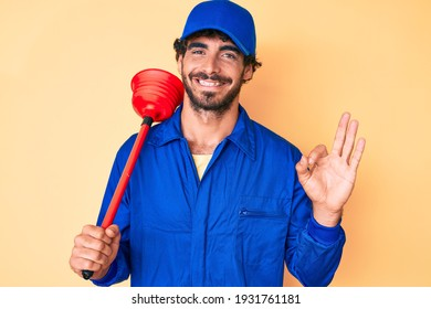 Handsome young man with curly hair and bear wearing plumber uniform holding toilet plunger doing ok sign with fingers, smiling friendly gesturing excellent symbol